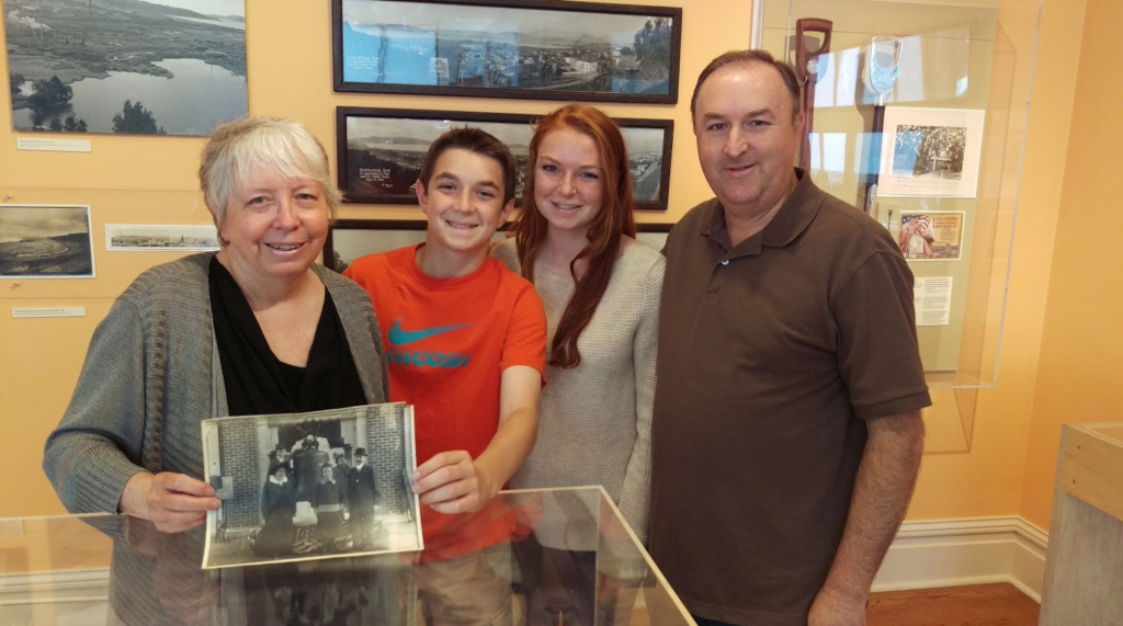 Three generations of the Rossi family: Rose Marie poses with her nephew Ron Forsell and grandchildren Grace and Matt, while holding a photo of her own mother and grandfather at the PPIE.